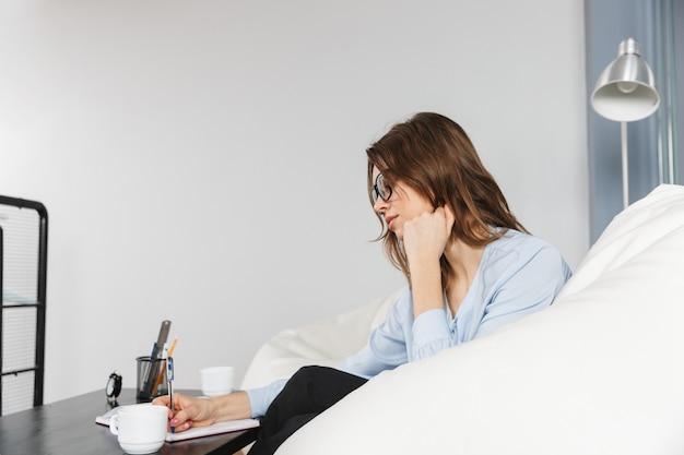 Mulher de negócios jovem e bonita sentada em um sofá no escritório, fazendo anotações