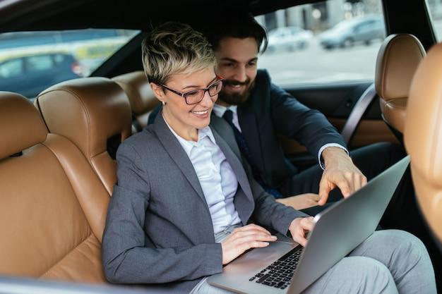 Mulher de negócios jovem e seu assistente sentado na limusine, conversando e trabalhando.