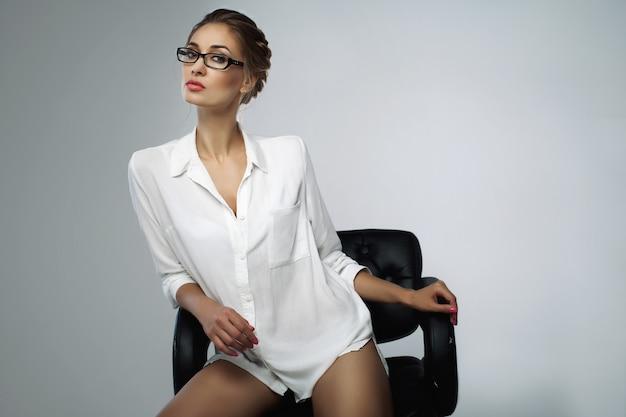 Mulher de negócios jovem elegante bonita sentada na cadeira do escritório de couro preto