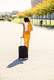 Mulher de negócios jovem elegante terno amarelo elegante se apressa para uma reunião de negócios e puxa uma mala, vista de trás.