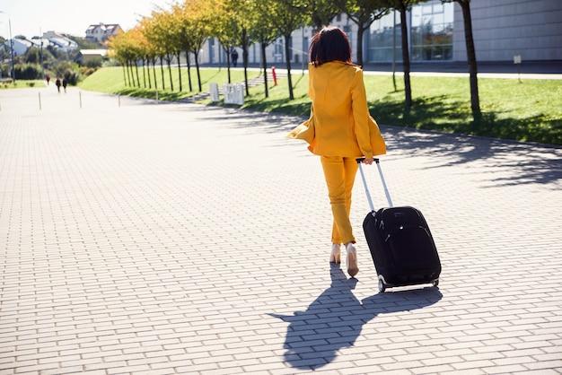Mulher de negócios jovem elegante terno amarelo elegante se apressa para uma reunião de negócios e puxa uma mala