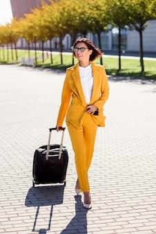 Mulher de negócios jovem elegante terno amarelo elegante se apressa para uma reunião de negócios, fala no smartphone e puxa uma mala. mulher de negócios atraente indo em uma viagem de negócios, puxando sua mala.