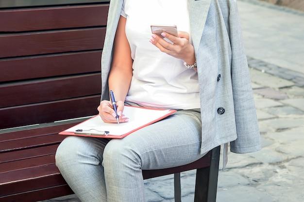 Mulher de negócios jovem elegante usando smartphone sentado no banco ao ar livre.