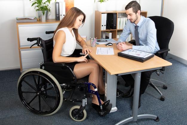 Mulher de negócios jovem em cadeira de rodas, trabalhando com um colega no escritório
