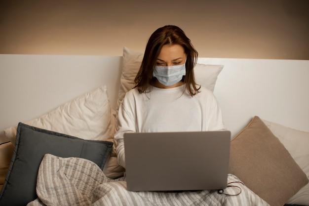 Mulher de negócios jovem em médico sentado na cama