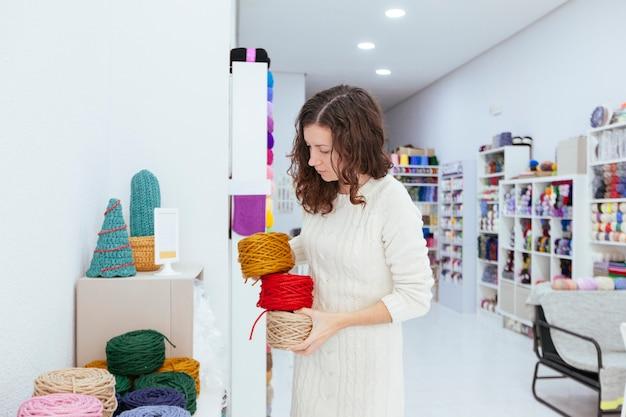 Mulher de negócios jovem em sua própria loja de varejo, pegando os fios de lã