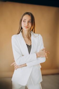 Mulher de negócios jovem em terno branco no estúdio