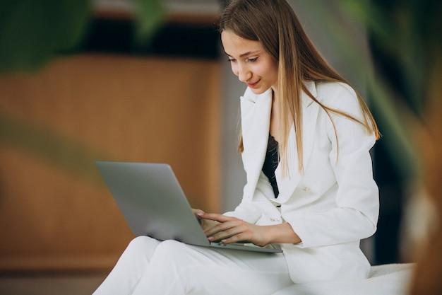 Mulher de negócios jovem em terno branco, trabalhando em um computador