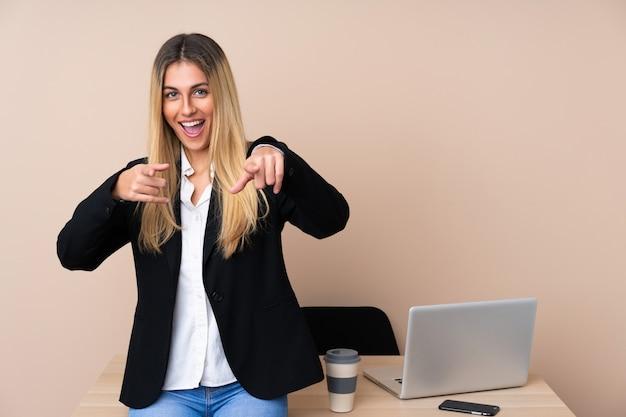 Mulher de negócios jovem em um escritório aponta o dedo para você