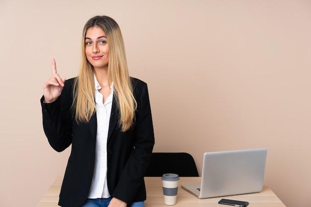 Mulher de negócios jovem em um escritório, apontando com o dedo indicador uma ótima idéia