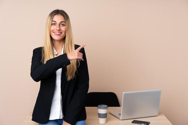 Mulher de negócios jovem em um escritório, apontando o dedo para o lado