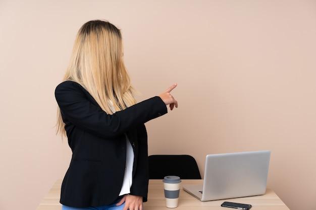 Mulher de negócios jovem em um escritório, apontando para trás com o dedo indicador