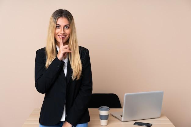 Mulher de negócios jovem em um escritório, fazendo o gesto de silêncio