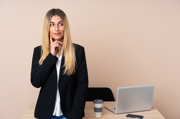Mulher de negócios jovem em um escritório pensando uma idéia