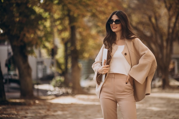 Mulher de negócios jovem em um terno de negócio com o laptop na rua