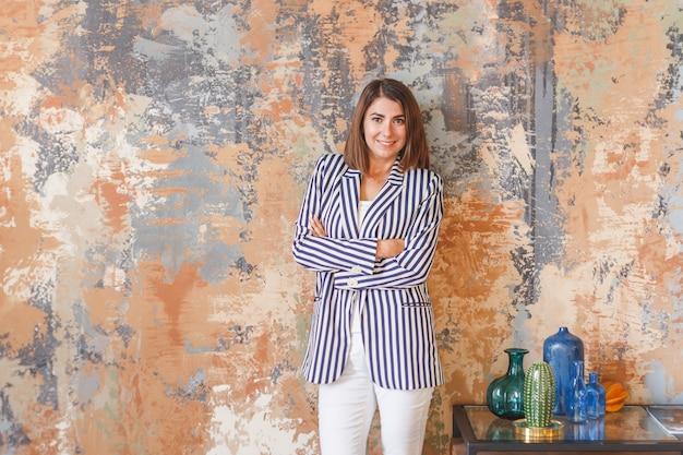 Mulher de negócios jovem em uma jaqueta listrada em pé com os braços cruzados
