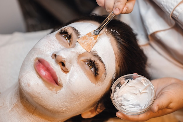 Mulher de negócios jovem encantadora relaxando depois do trabalho no centro de spa de bem-estar fazendo procedimentos faciais sorrindo.