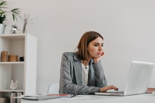 Mulher de negócios jovem entediada com roupa cinza olha para a tela do laptop em seu local de trabalho.