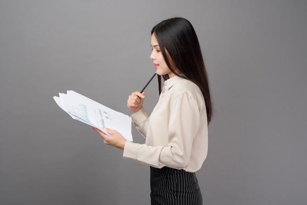 Mulher de negócios jovem está analisando o plano de negócios sobre fundo cinza
