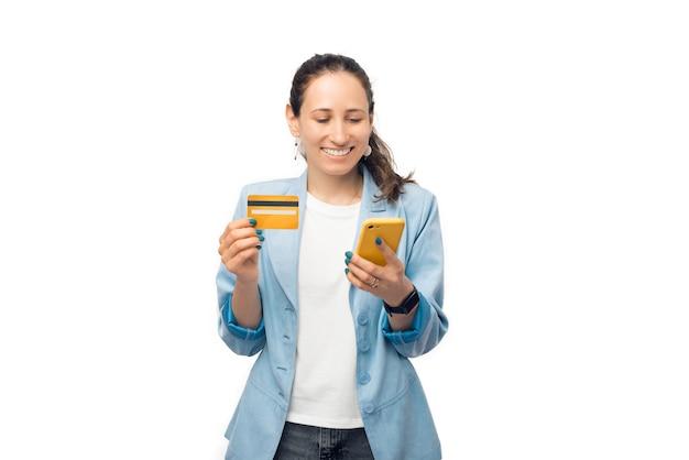 Mulher de negócios jovem está segurando seu cartão de crédito e telefone usando o banco móvel.