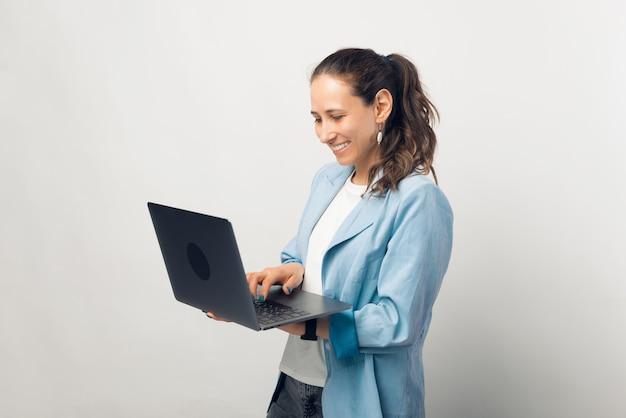 Mulher de negócios jovem está trabalhando de pé em seu laptop em um estúdio.
