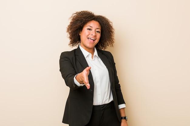 Mulher de negócios jovem esticando a mão na câmera em gesto de saudação.