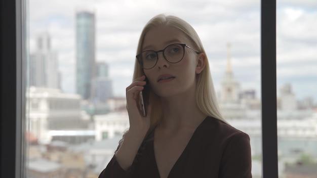 Mulher de negócios jovem falando ao telefone perto de uma grande janela com vista para o centro da cidade. mulher de negócios no escritório. close-up, 4k uhd.