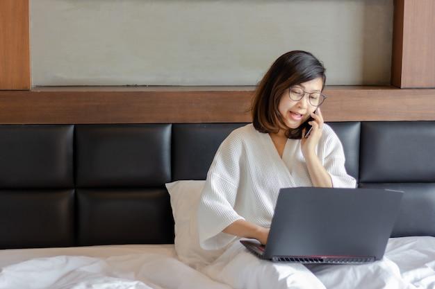 Mulher de negócios jovem falando no telefone e usando o smartphone na cama enquanto trabalha em casa