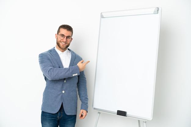 Mulher de negócios jovem fazendo uma apresentação em quadro branco isolado na parede branca apontando para trás
