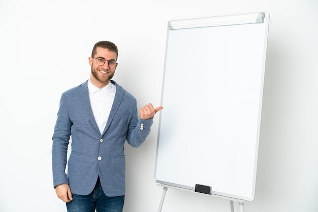 Mulher de negócios jovem fazendo uma apresentação no quadro branco isolado na parede branca apontando para o lado para apresentar um produto