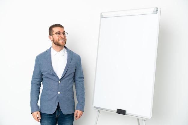 Mulher de negócios jovem fazendo uma apresentação no quadro branco isolado na parede branca pensando uma ideia enquanto olha para cima