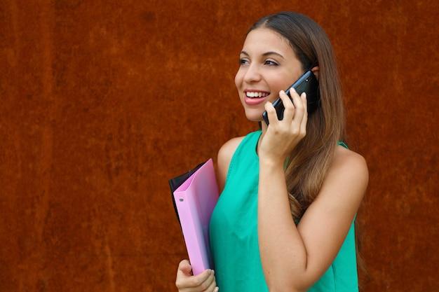 Mulher de negócios jovem feliz chamando com o telefone em fundo ferrugem. copie o espaço.