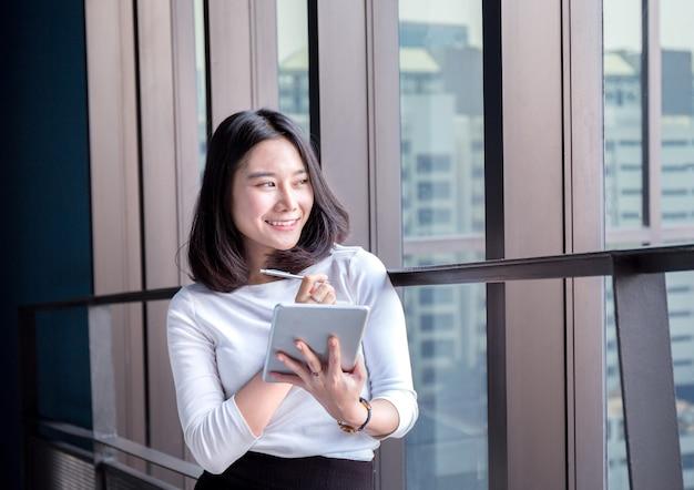 Mulher de negócios jovem feliz e bem sucedida sorrir com resultado em tablet digital