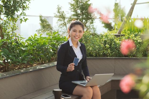 Mulher de negócios jovem feliz retrato segurando cartão de crédito e laptop fazendo oder on-line, conceito de compra isolado ao ar livre, fora do plano de fundo. expressões faciais positivas, emoções. cliente sorridente