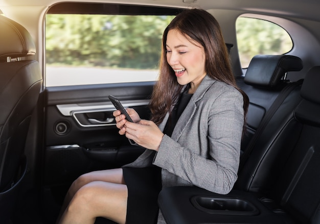 Mulher de negócios jovem feliz usando um smartphone enquanto está sentado no banco de trás do carro