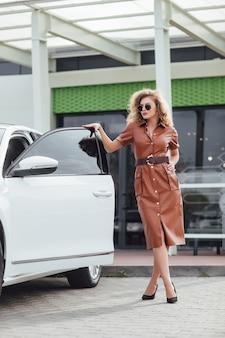 Mulher de negócios jovem feliz usando vestido e salto alto, sorrindo e em pé perto de seu carro branco em uma cidade europeia em um dia ensolarado de verão