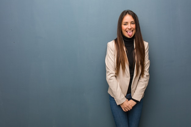 Mulher de negócios jovem funnny e amigável mostrando a língua