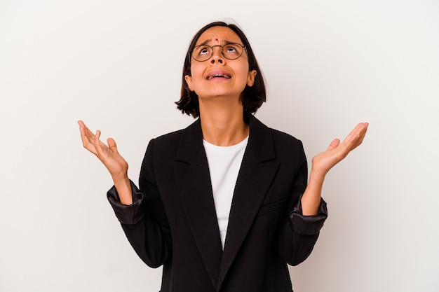Mulher de negócios jovem indiana isolada no fundo branco, gritando para o céu, olhando para cima, frustrada.