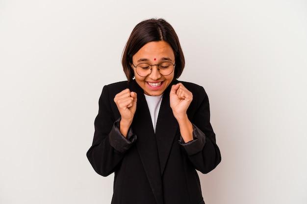 Mulher de negócios jovem indiana isolada no fundo branco, levantando o punho, sentindo-se feliz e bem-sucedido. conceito de vitória.