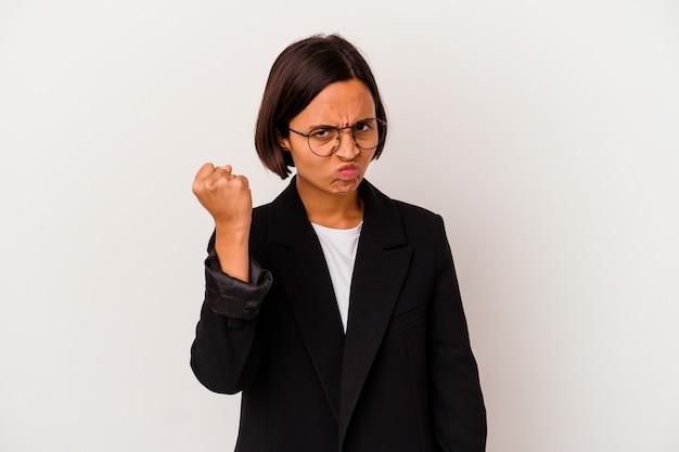 Mulher de negócios jovem indiana isolada no fundo branco, mostrando o punho para a câmera, expressão facial agressiva.