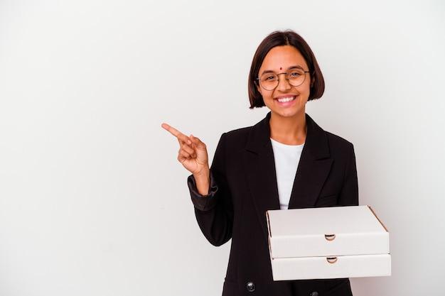Mulher de negócios jovem indiana segurando pizzas isoladas, sorrindo e apontando de lado, mostrando algo no espaço em branco.