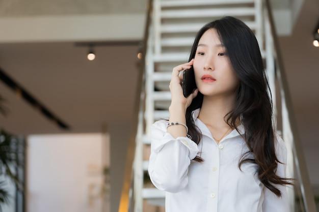 Mulher de negócios jovem inteligente, vestindo camisa branca e brim azul, chamando o telefone móvel em pé na frente da escada em conceitual de negócios bem sucedido