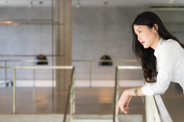 Mulher de negócios jovem inteligente, vestindo camisa branca, sorrindo e posando enquanto inclinando-se contra a escada em conceitual de negócio bem sucedido
