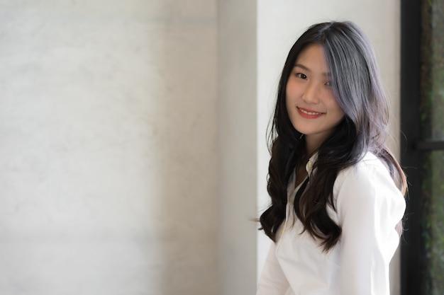Mulher de negócios jovem inteligente, vestindo camisa branca, sorrindo enquanto posava e olhando para a câmera em conceitual de negócio bem sucedido