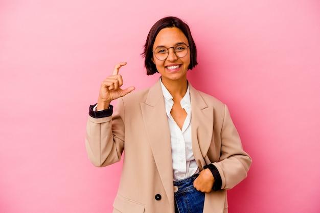 Mulher de negócios jovem isolada na parede rosa segurando algo pequeno com os indicadores, sorrindo e confiante