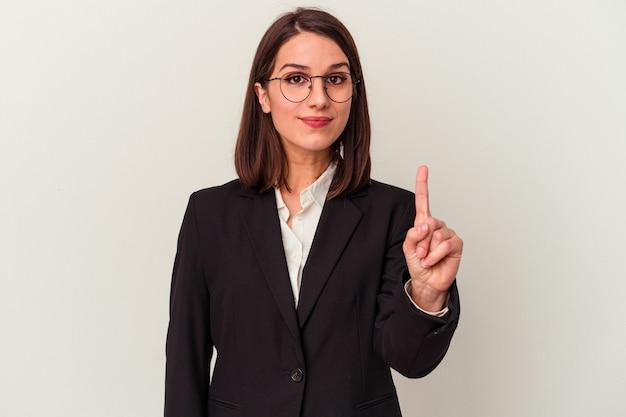 Mulher de negócios jovem isolada no fundo branco, mostrando o número um com o dedo.