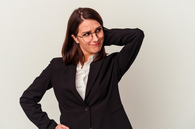 Mulher de negócios jovem isolada no fundo branco, tocando a parte de trás da cabeça, pensando e fazendo uma escolha.