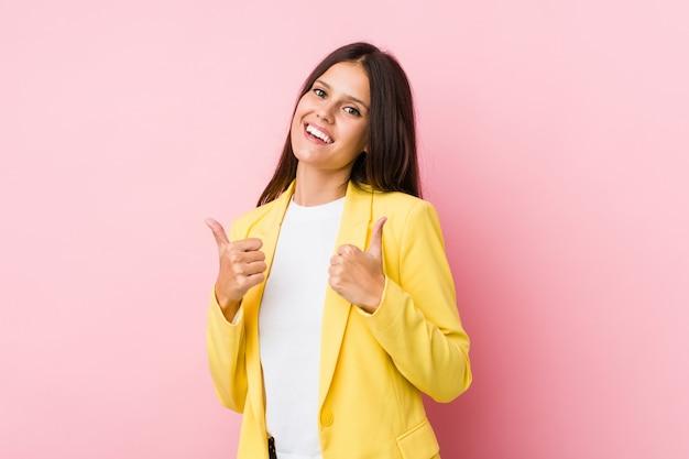 Mulher de negócios jovem levantando os dois polegares, sorrindo e confiante.