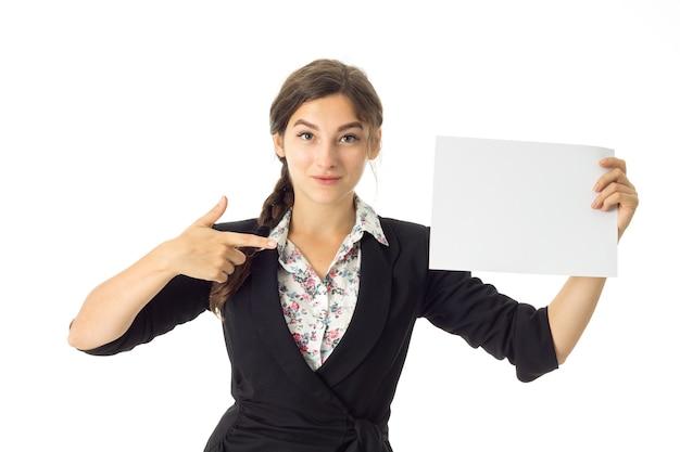 Mulher de negócios jovem morena elegante de uniforme com um cartaz branco nas mãos isoladas na parede branca