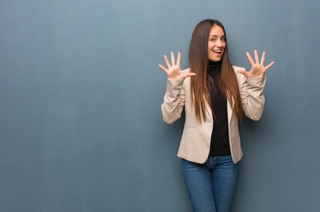 Mulher de negócios jovem mostrando o número dez